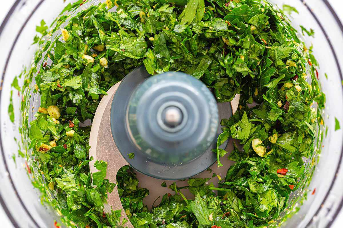 Herbs, spices and oils mixed together in a food processor to make chimichurri with avocados for skirt steak