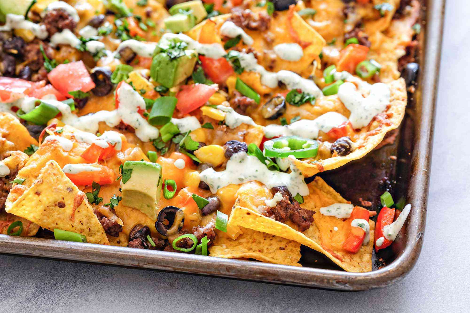 Corner of a sheet pan loaded with homemade nachos