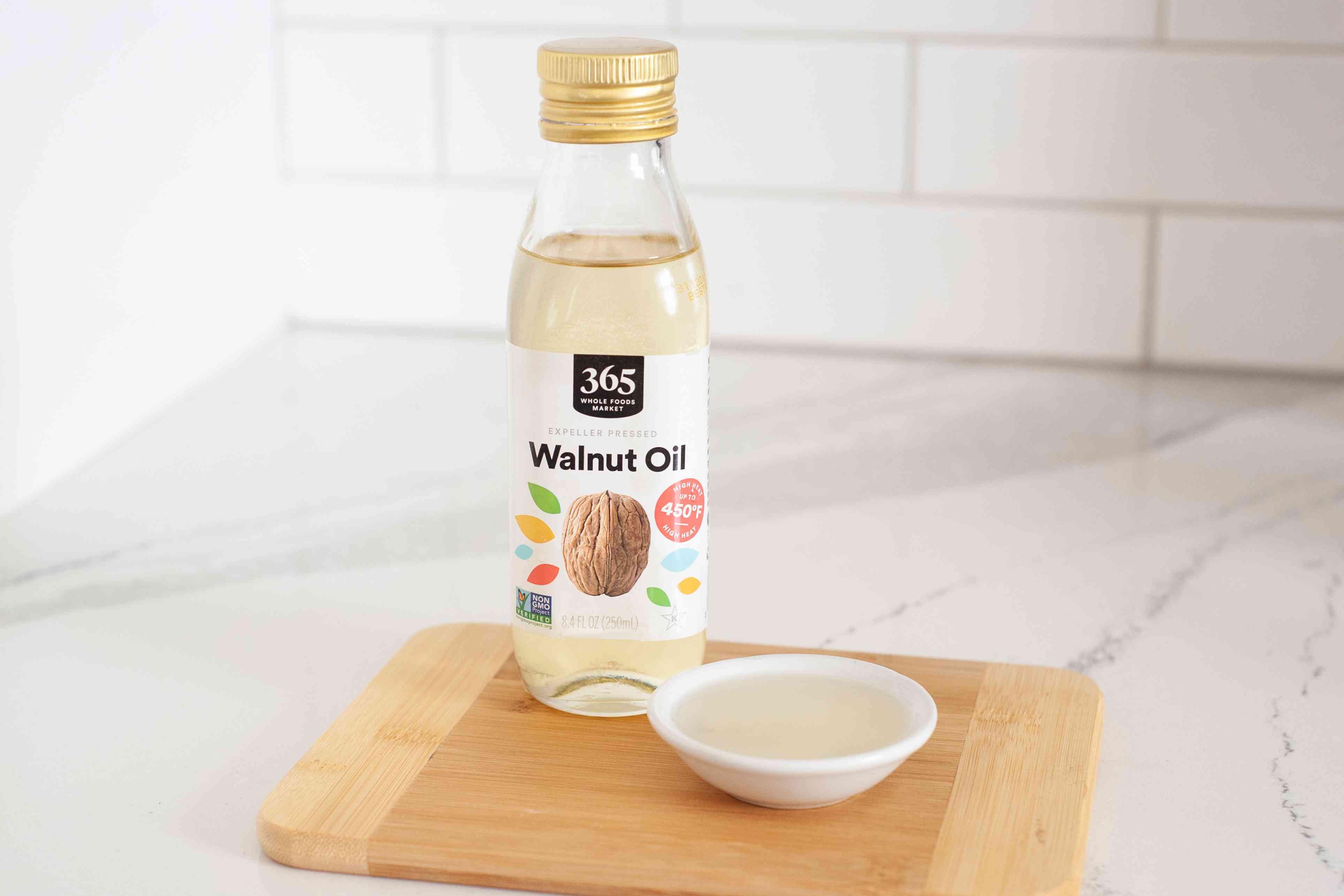 Walnut oil on wood cutting board white background