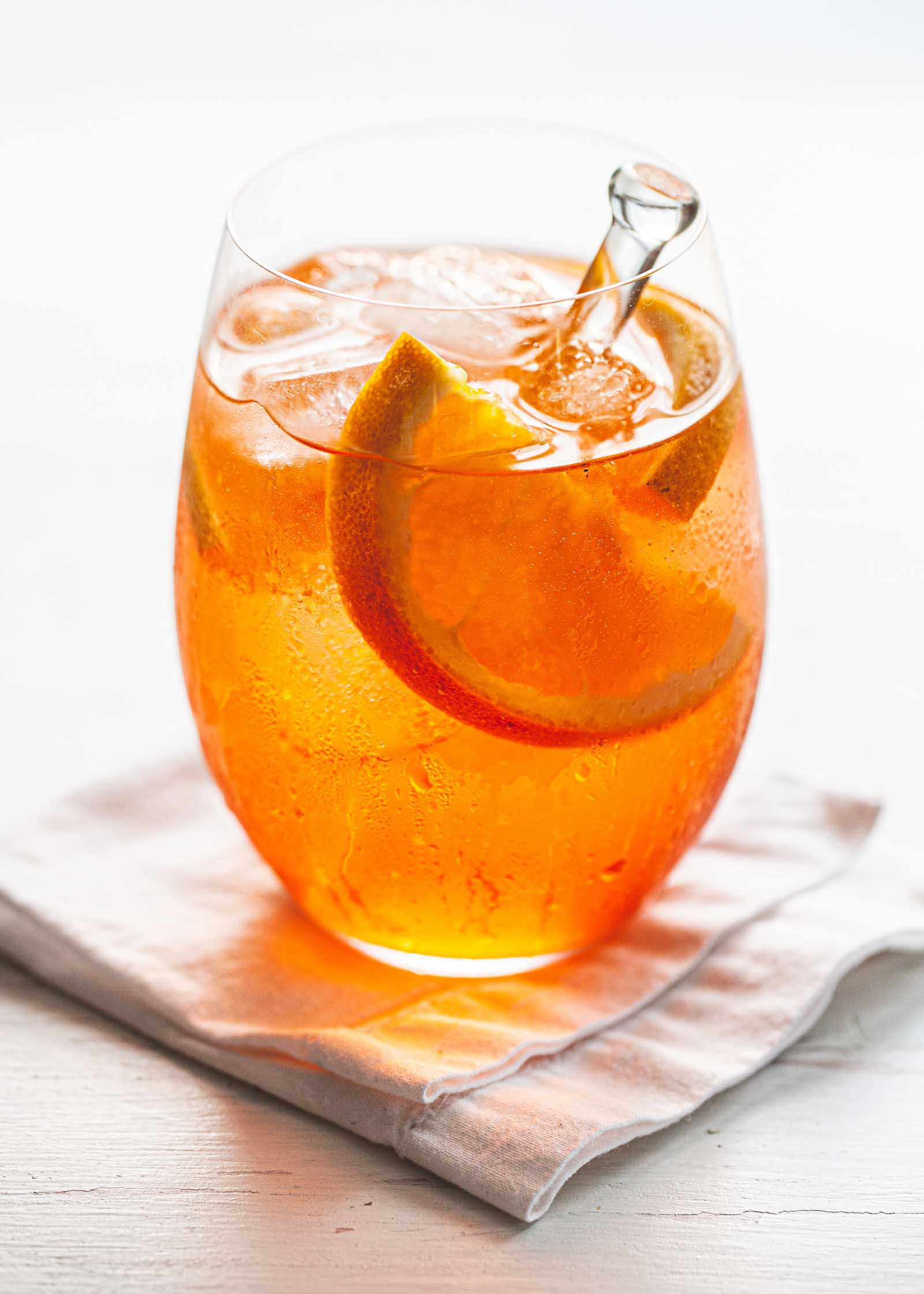 Aperol spritz cocktail in a wine glass with ice, orange slices and a stir stick.