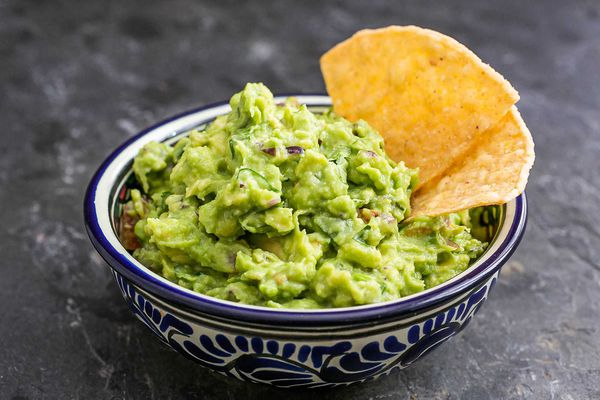 Authentic guacamole in a bowl with chips