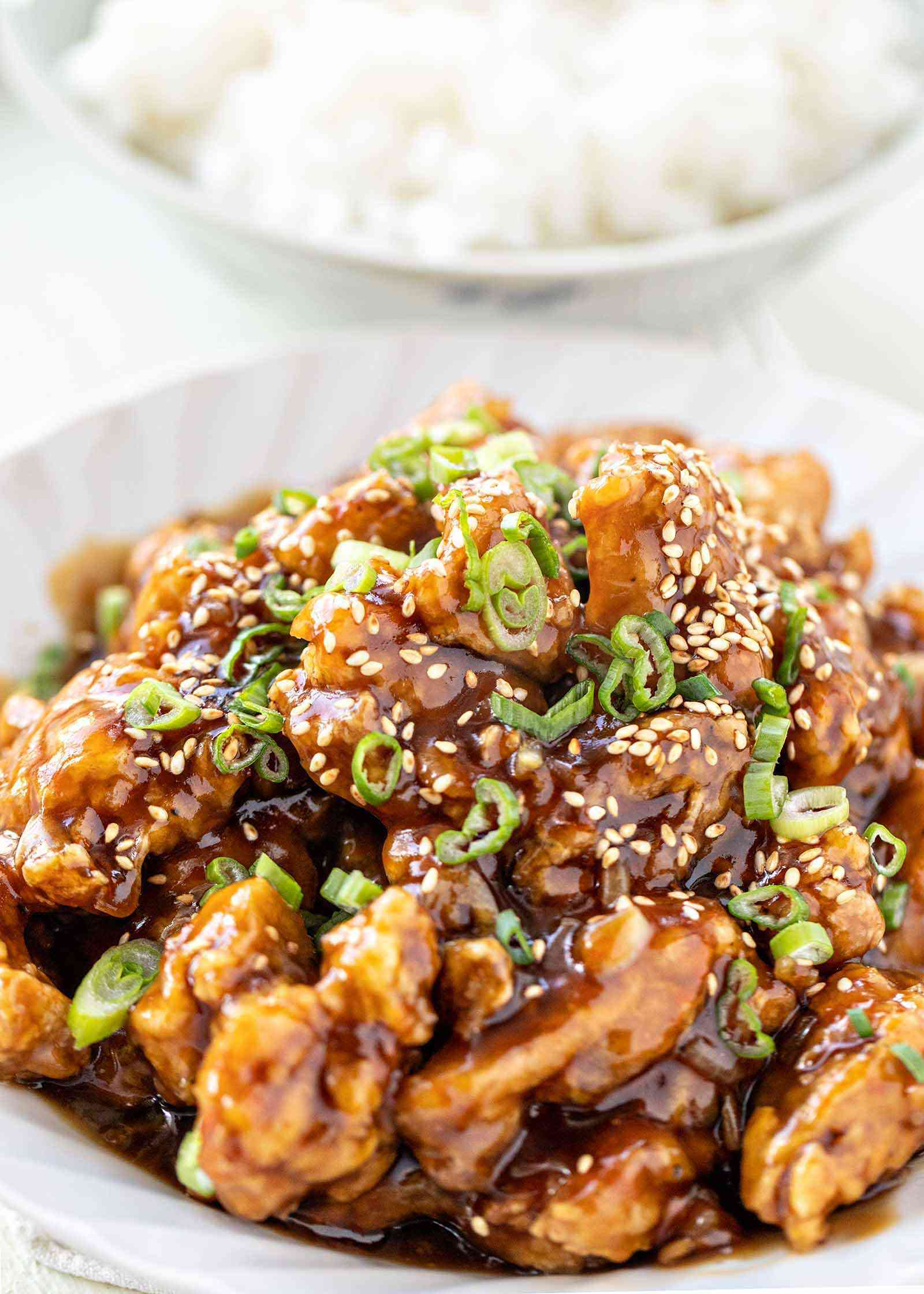 Vertical close up photo of take out chinese orange chicken topped with sesame seeds and chopped scallions. A bowl of white rice is behind the orange chicken.