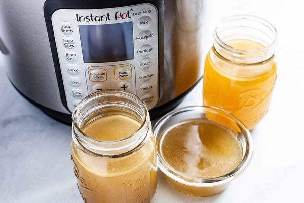 Instant Pot Chicken Stock - jars filled with chicken stock in front of an Instant Pot