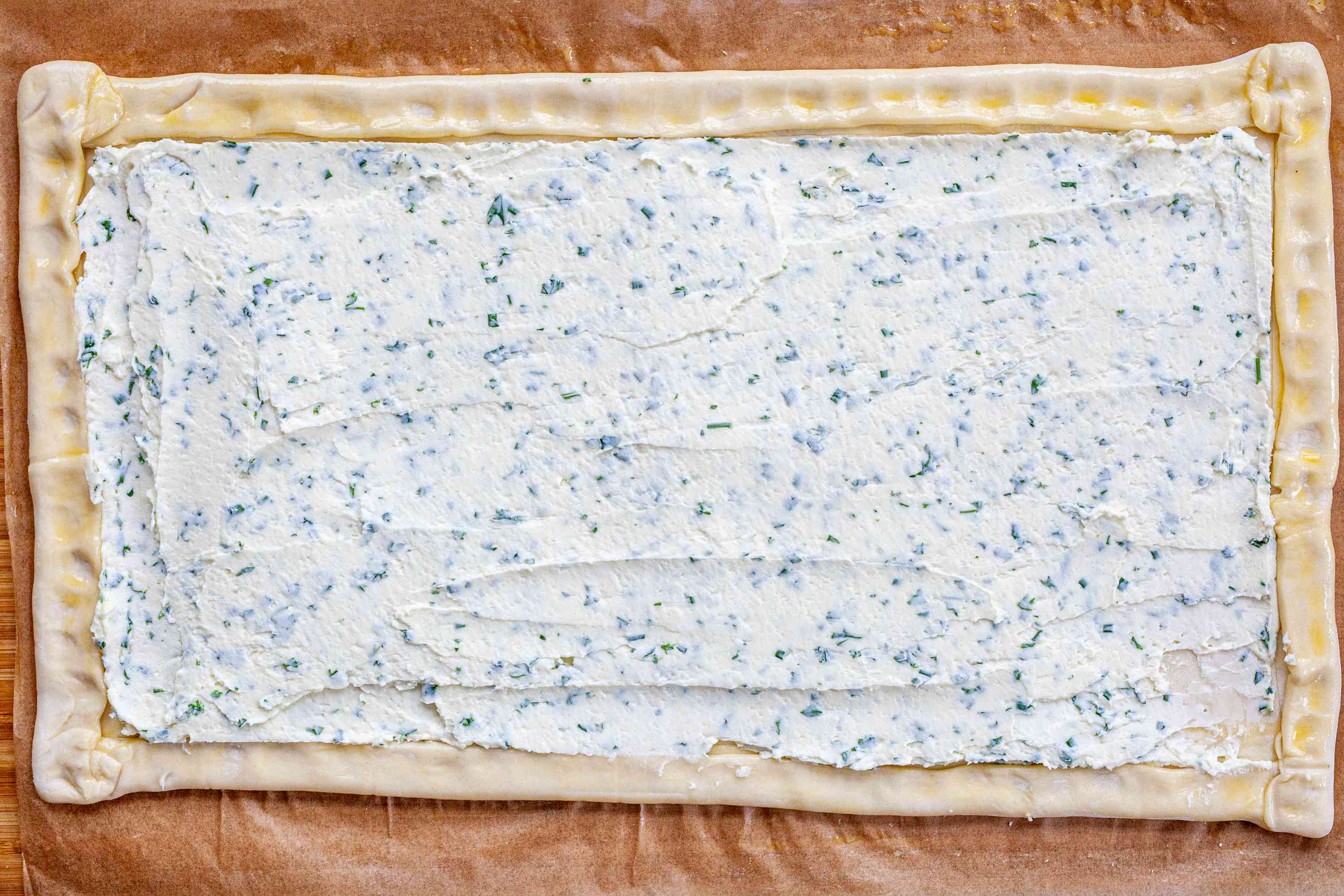 Goat cheese spread on puff pastry to make a Spring Asparagus Tart.