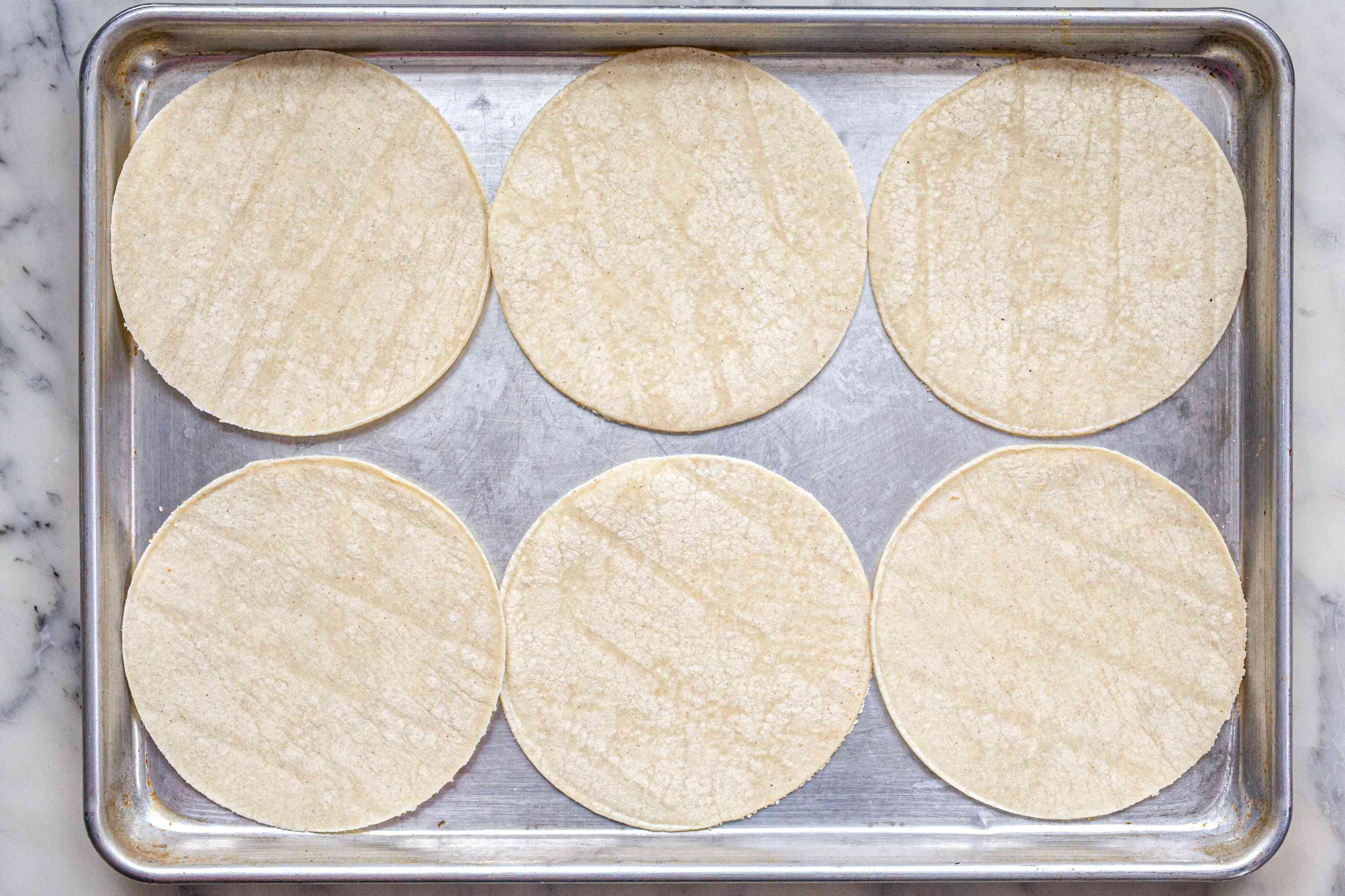 A sheet pan with tortillas on it to make homemade chips.