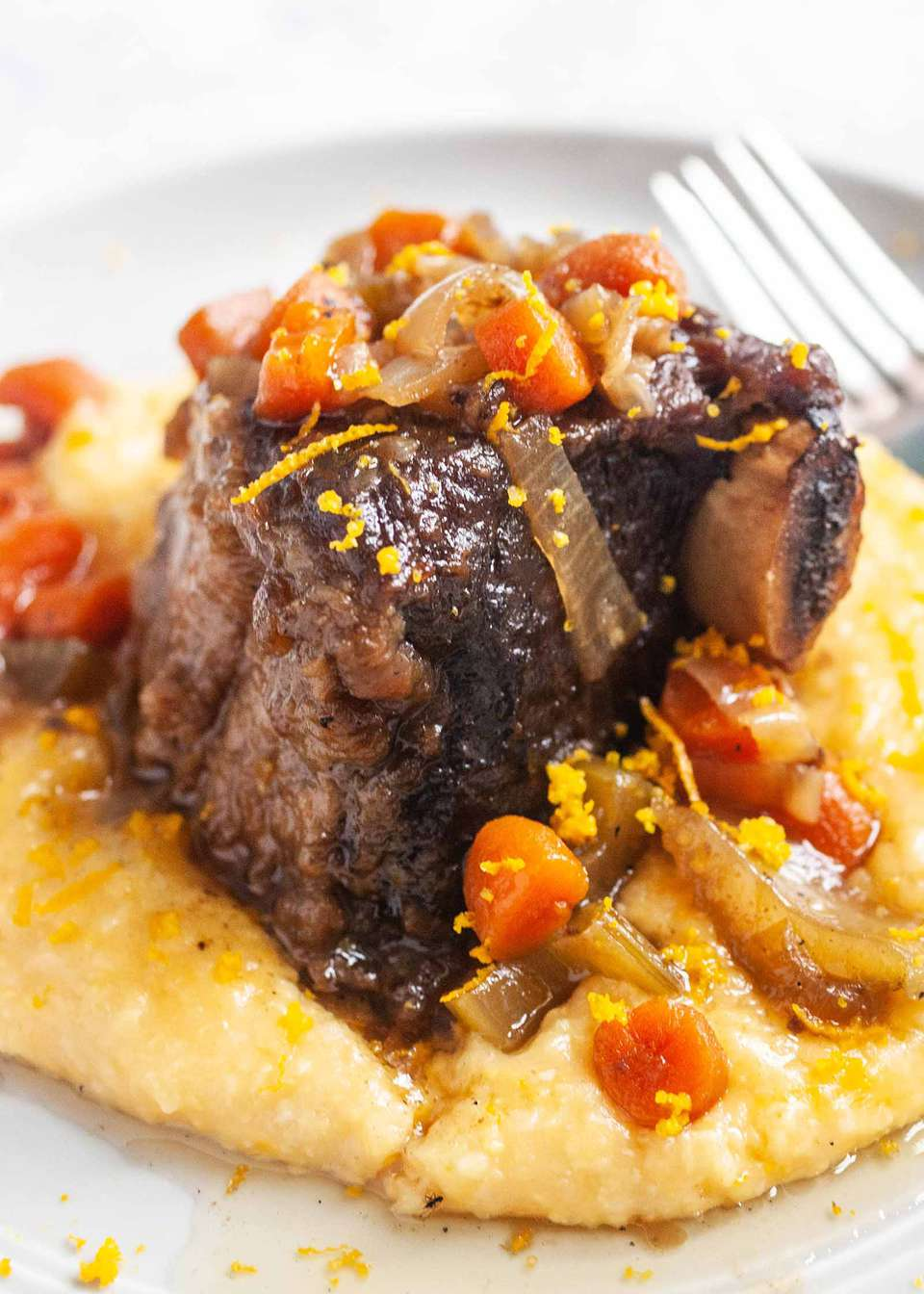 Crockpot Braised Beef Short Ribs with Polenta and carrots on a round plate