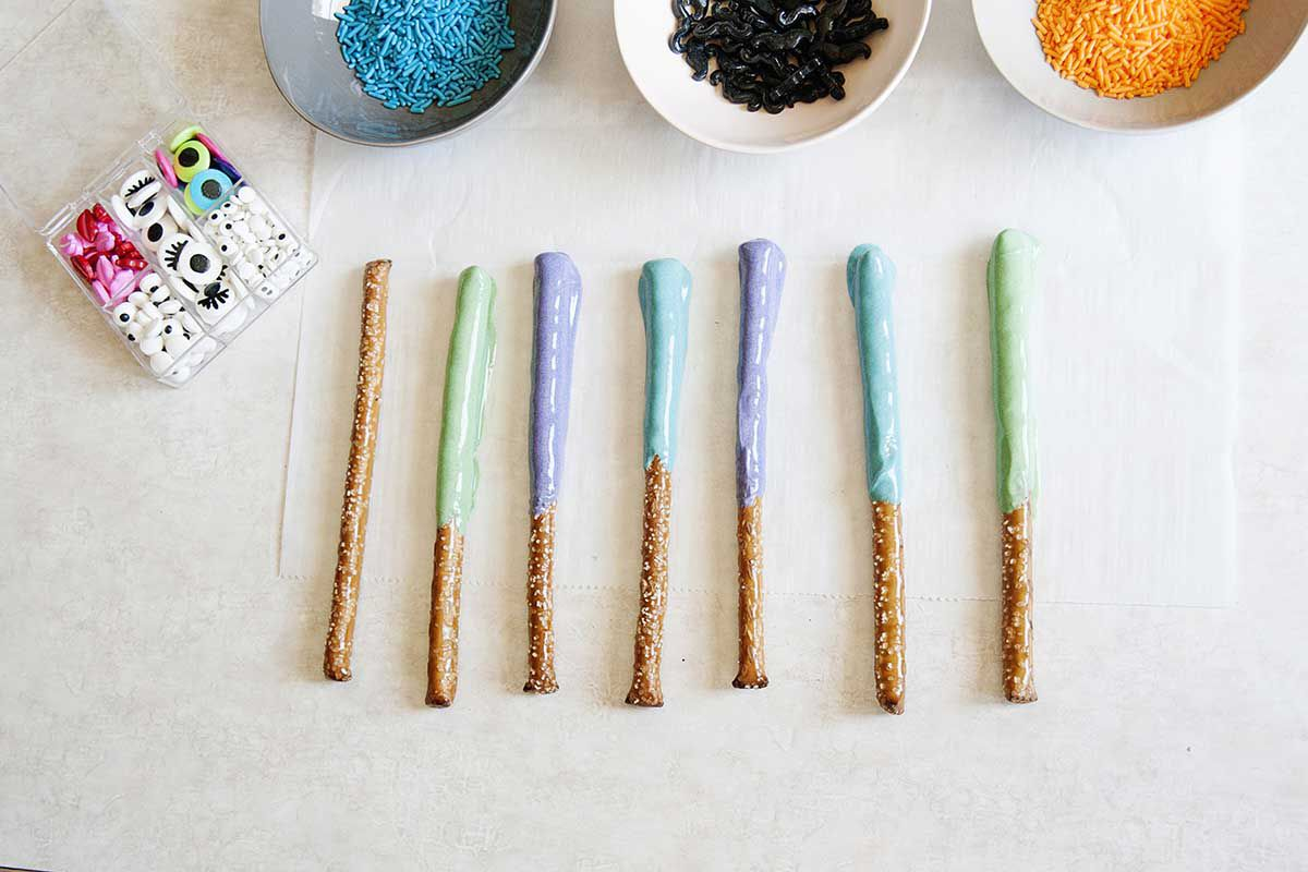 Easy Chocolate dipped pretzel rods in blue, green and purple on a counter top.