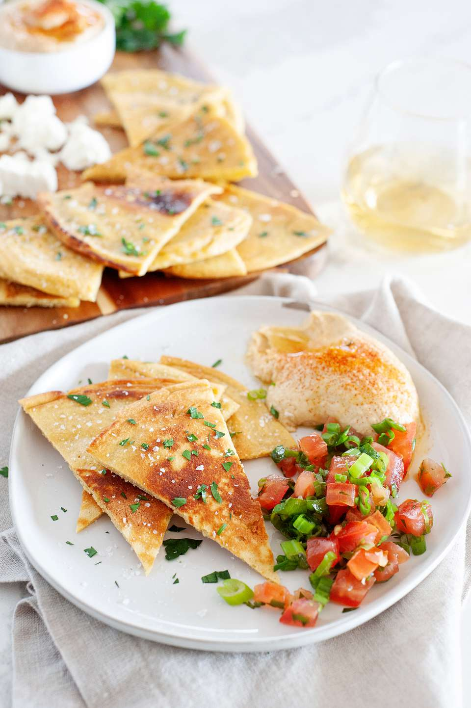 Socca—Gluten-Free Chickpea Flour Flatbread cut into triangles and on a plate with chopped vegetables.