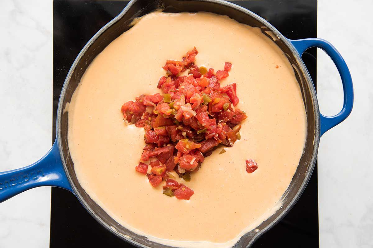 A black cast iron skillet will spices, milk and cheese being whisked together with a wooden spoon for easy homemade queso with tomatoes and rotel added in.