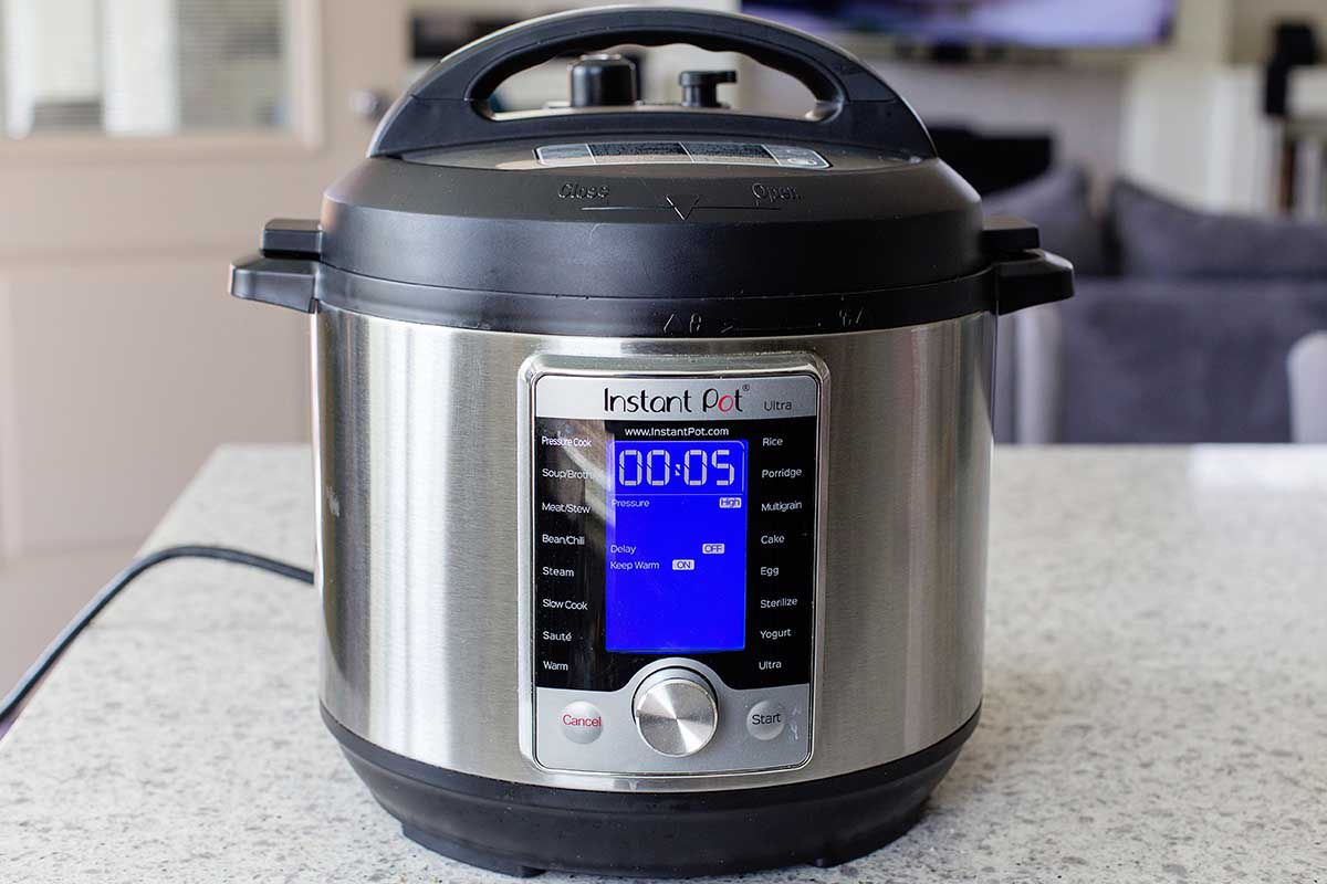 Instant Pot on a countertop with the timer set to 5 minutes.