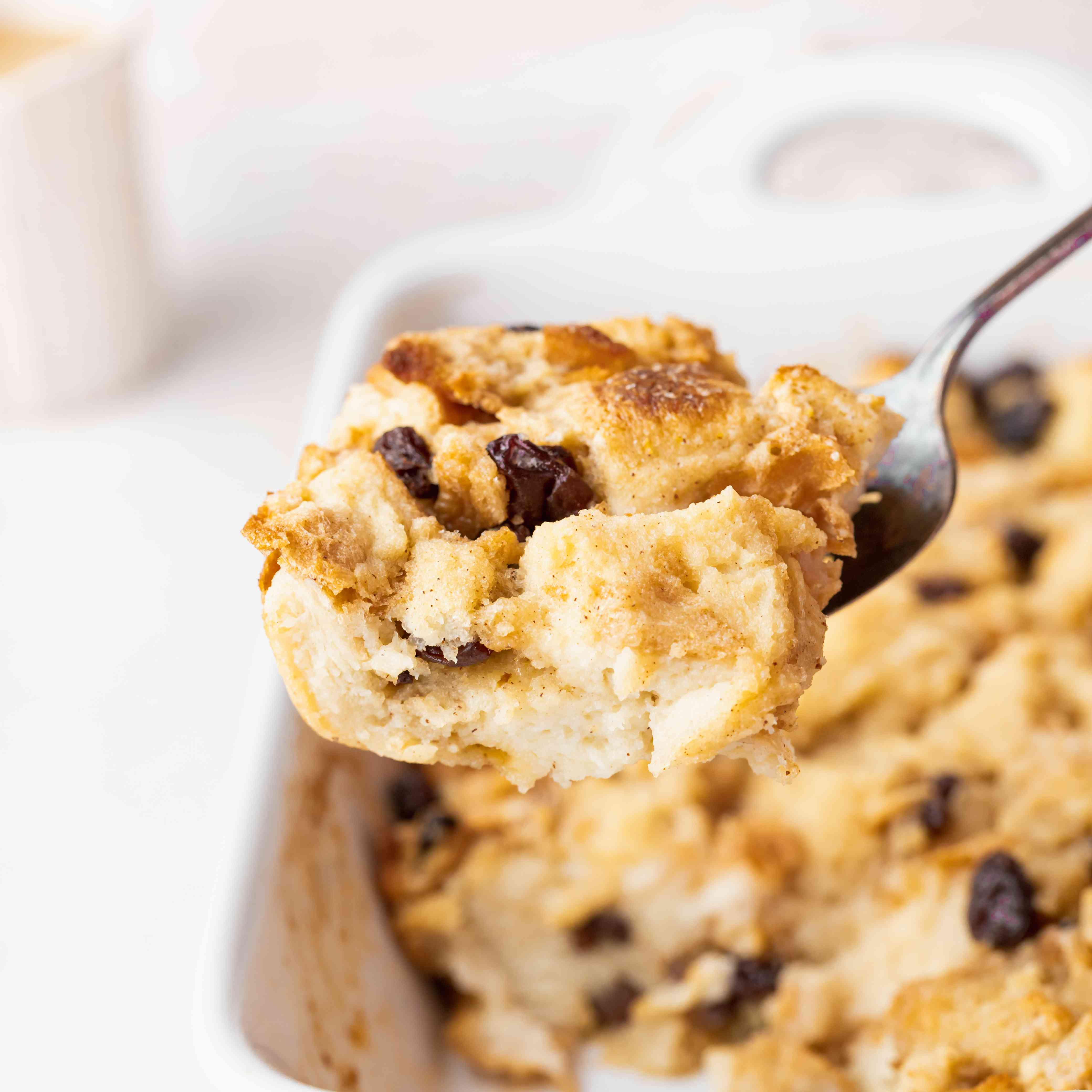 Scooping easy bread pudding out of a white casserole dish.