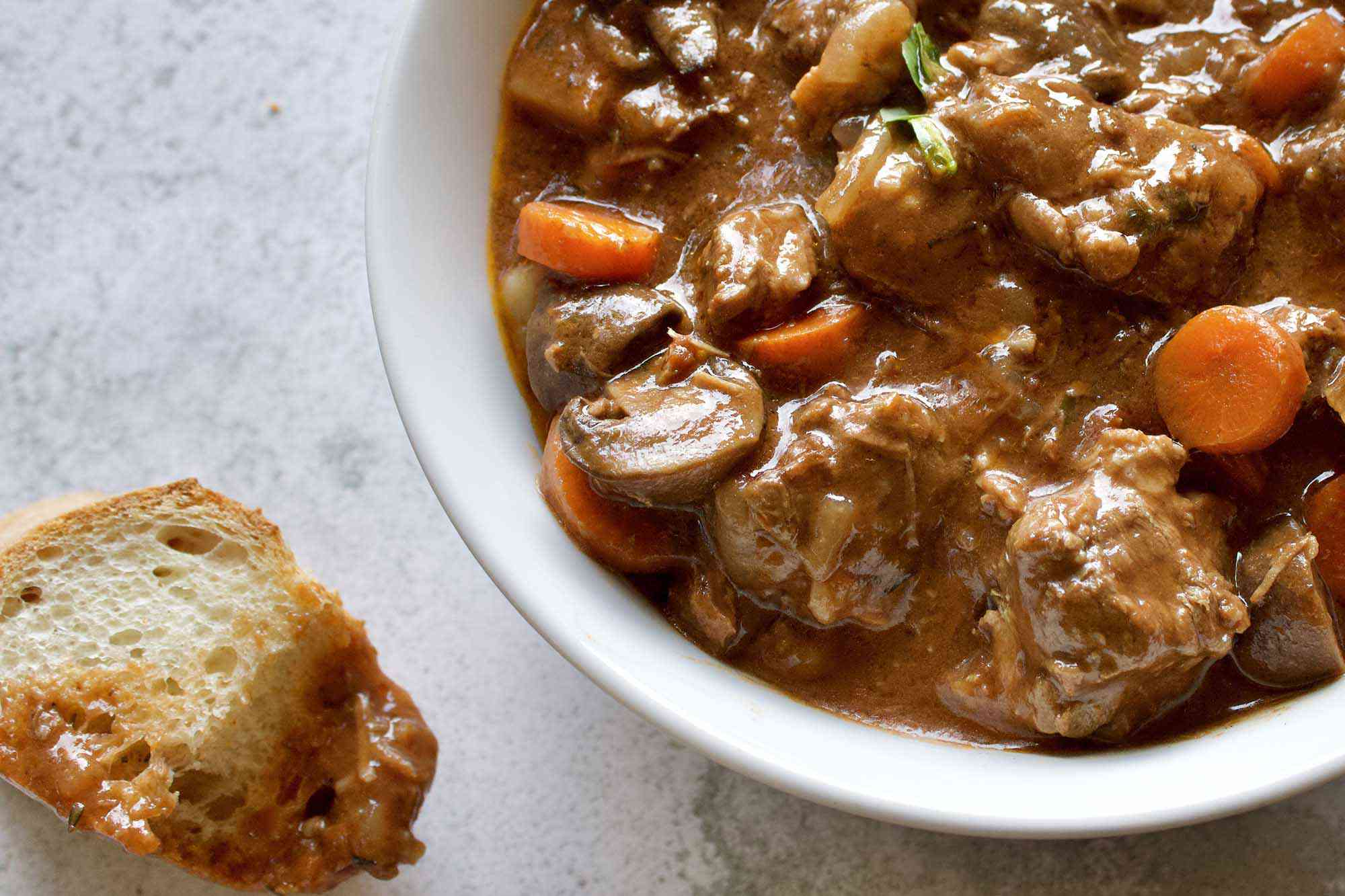 A slice of bread dipped into a bowl of Slow Cooker Beef Stew with Mushrooms, Onions and Carrots and set to the side.