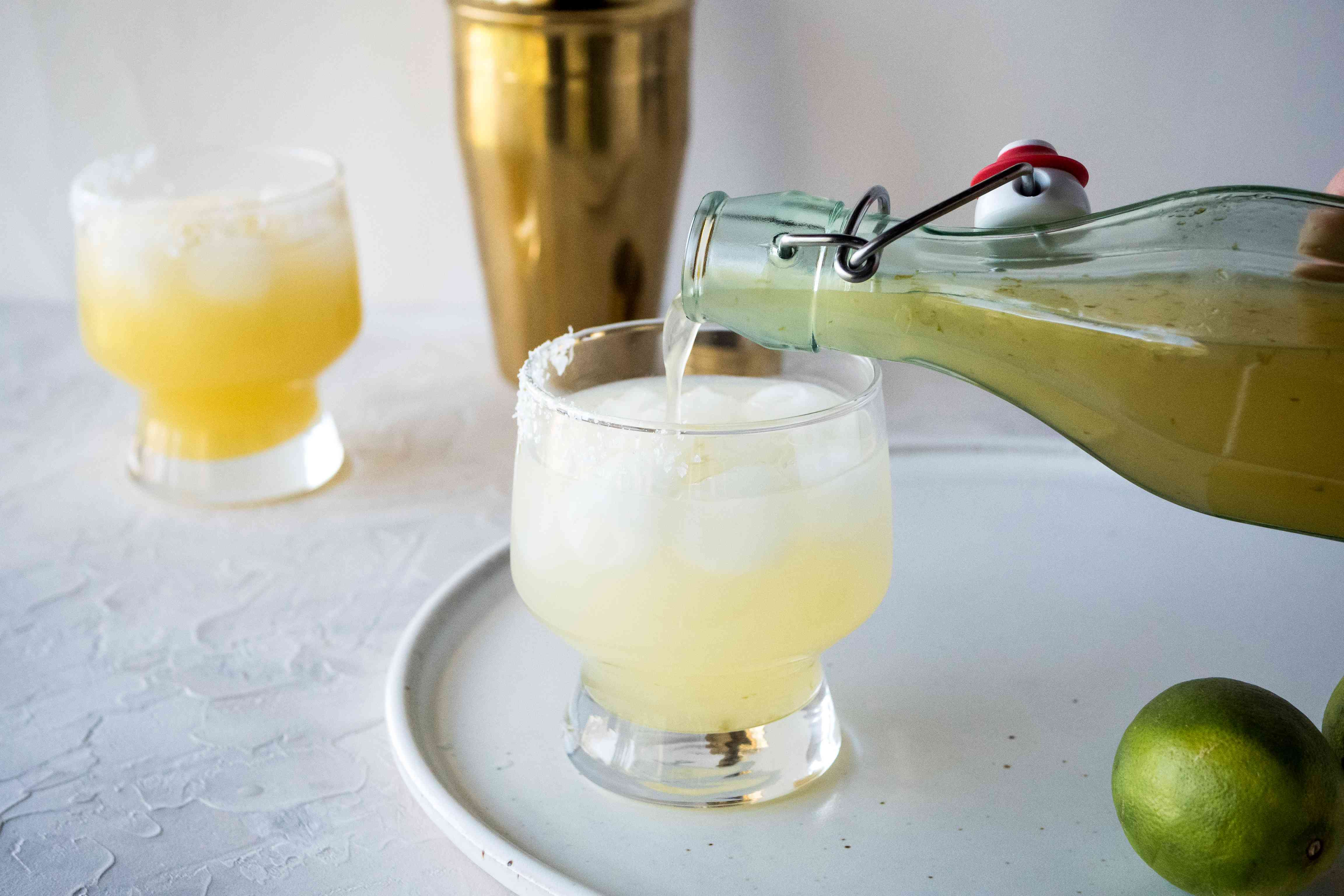 The BEST margarita mix recipe poured into a glass with ice to make a margarita.