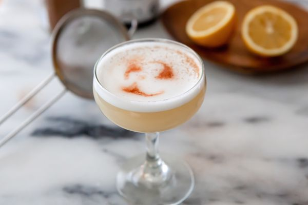 A coupe glass filled with an Authentic Peruvian Pisco Sour.