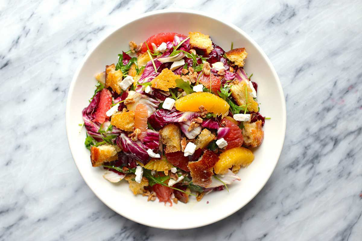 Citrus Salad on a white plate set on a marble background. Supremed orange and grapefruit, radicchio, croutons and feta cheese crumbles are visible.
