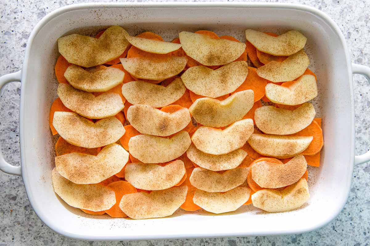 Matzo Side Dish for Passover - - white casserole dish with a layer of sweet potatoes on the bottom and a layer of apples on top sprinkled iwth cinnamon