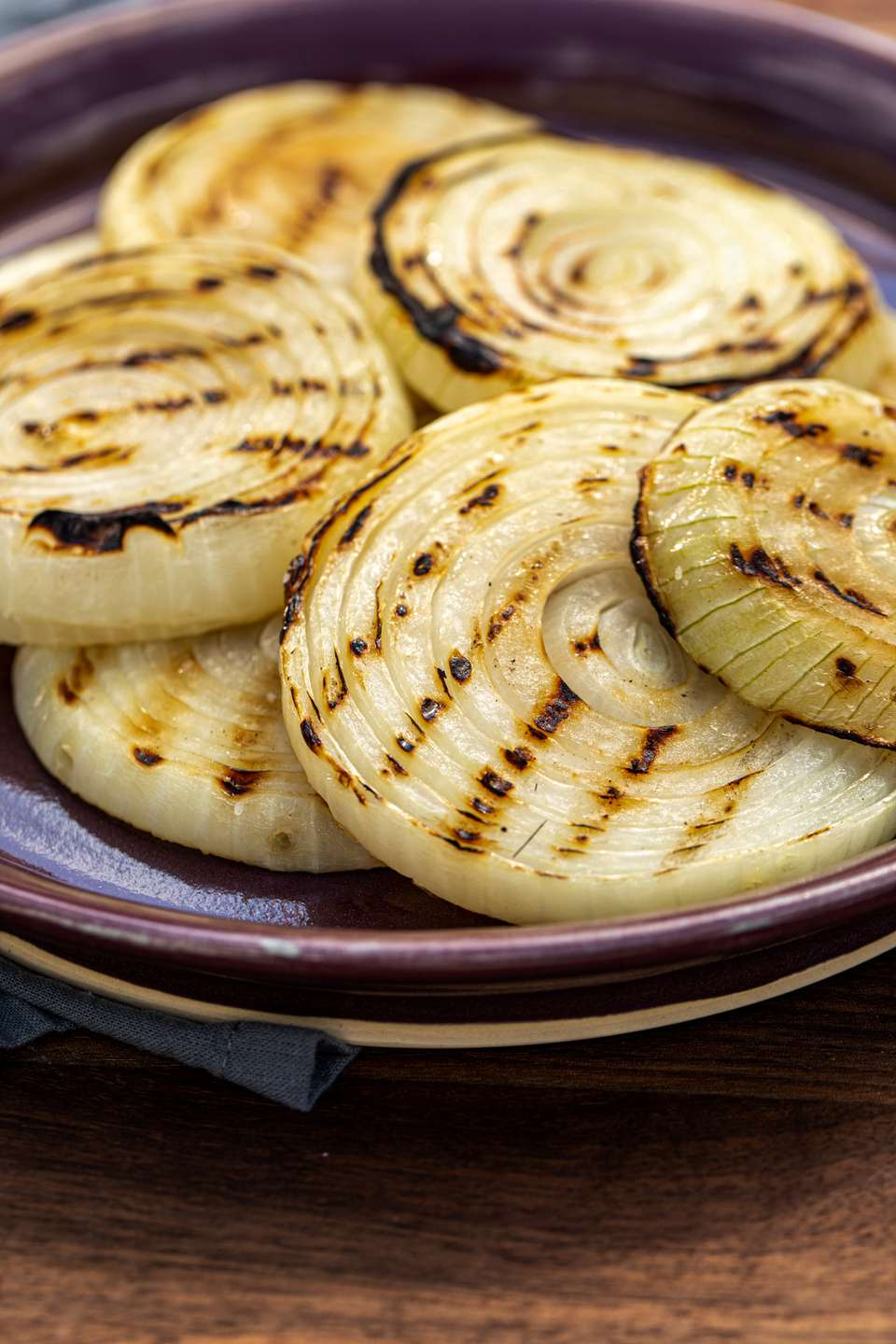 The best ever grilled onions piled on a purple rimmed platter.