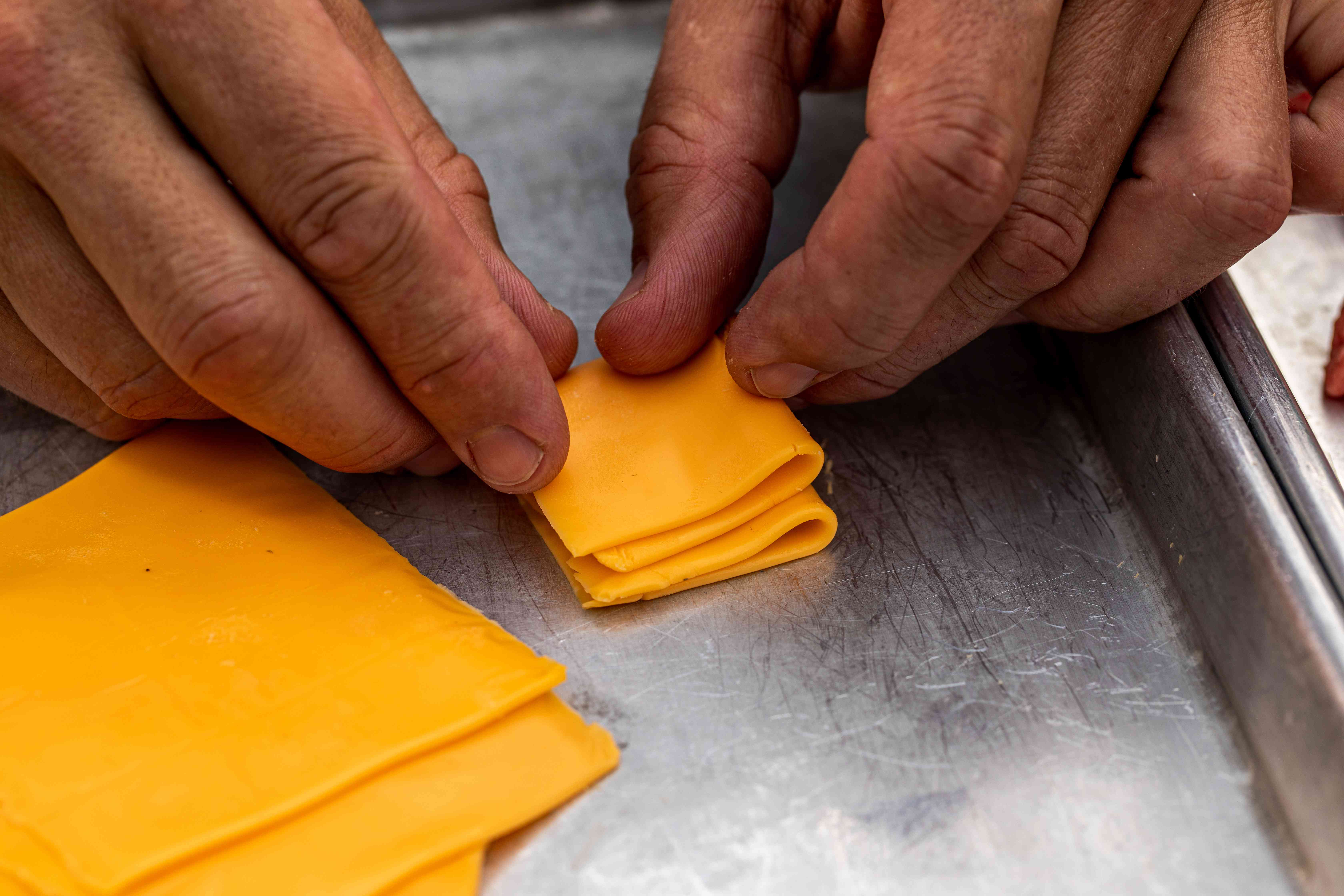 Folding sliced cheese into a square to show how to make a Jucy Lucy burger
