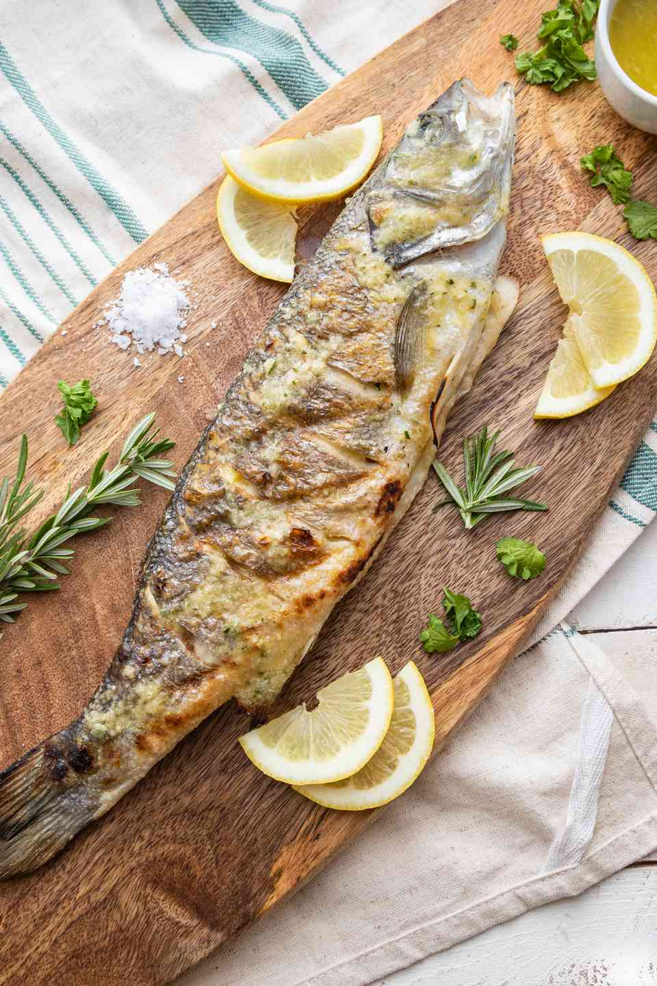 Overhead view of a whole branzino on a platter with lemon wedges and herbs.