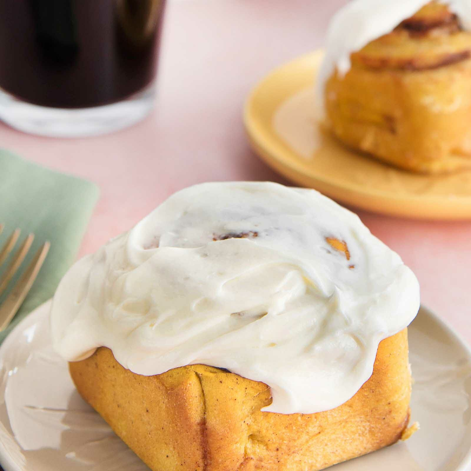 Homemade Pumpkin Cinnamon Rolls set on a small plate with a fork to the left and a second plate behind.