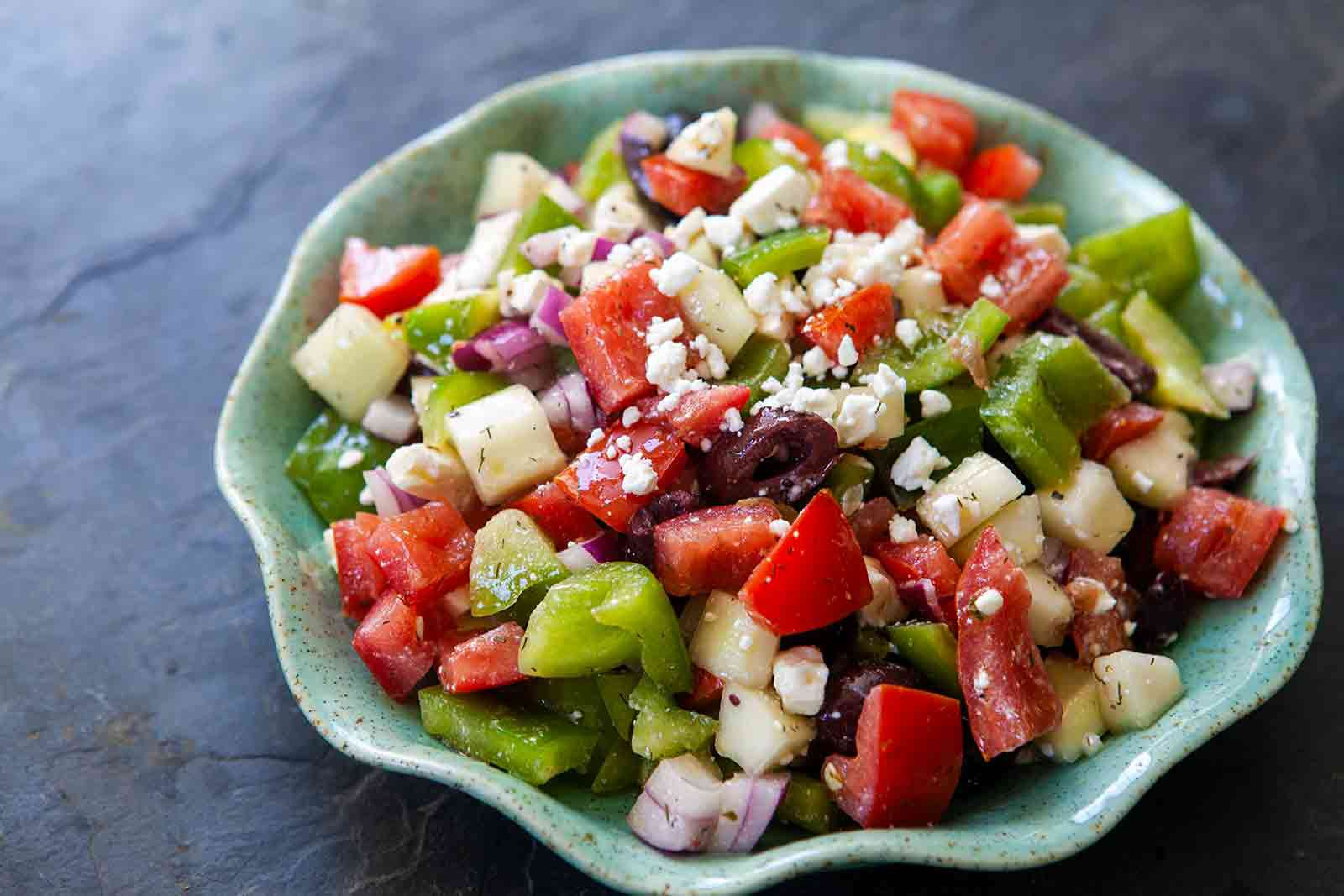 Easy Greek Salad tossed with greek salad dressing in a bowl