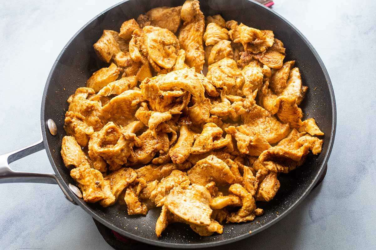 Sliced chicken cooked in a non-stick skillet to make easy stuffed pepper recipe.