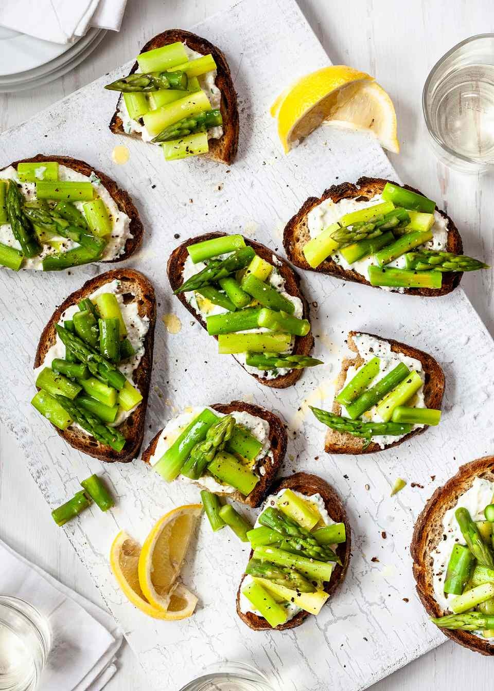 Asparagus Crostini Recipe - many bruschetta with asparagus and ricotta on a white background with lemon wedges