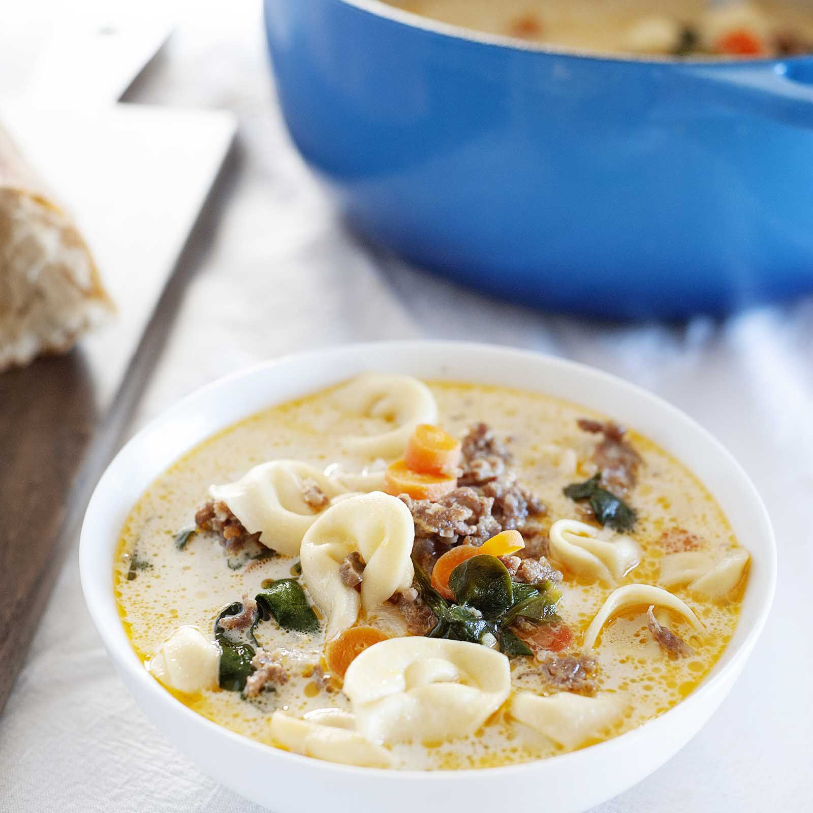 Best homemade creamy tortellini soup in a white bowl on a table with a white tablecloth. A blue dutch oven with soup and spoon inside is behind the bowl.