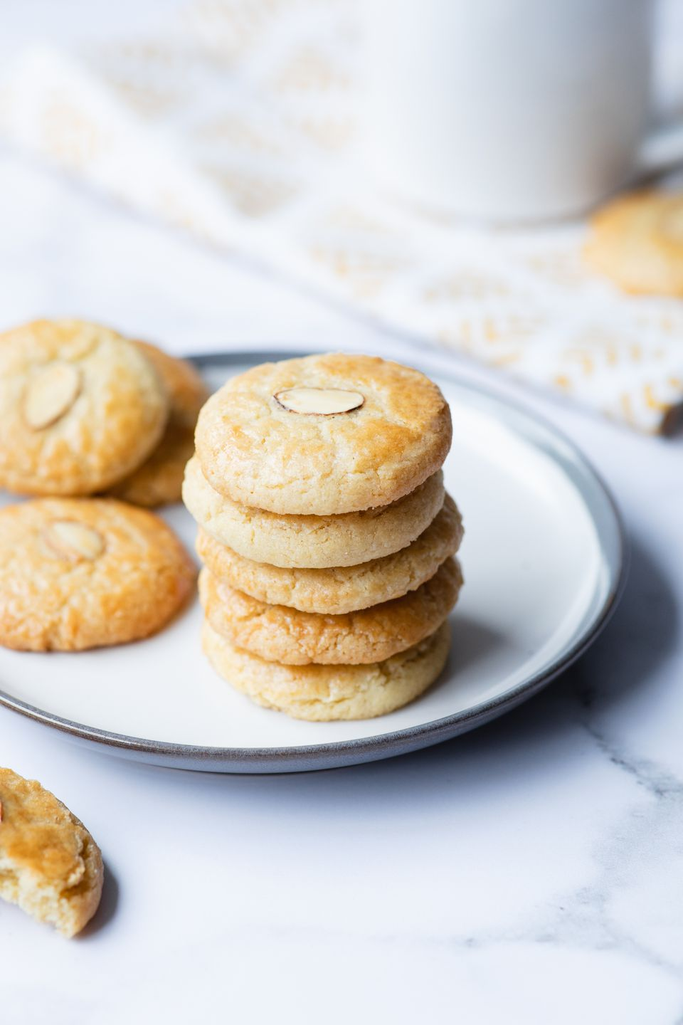 Almond cookies stacked and scattered on a plate.