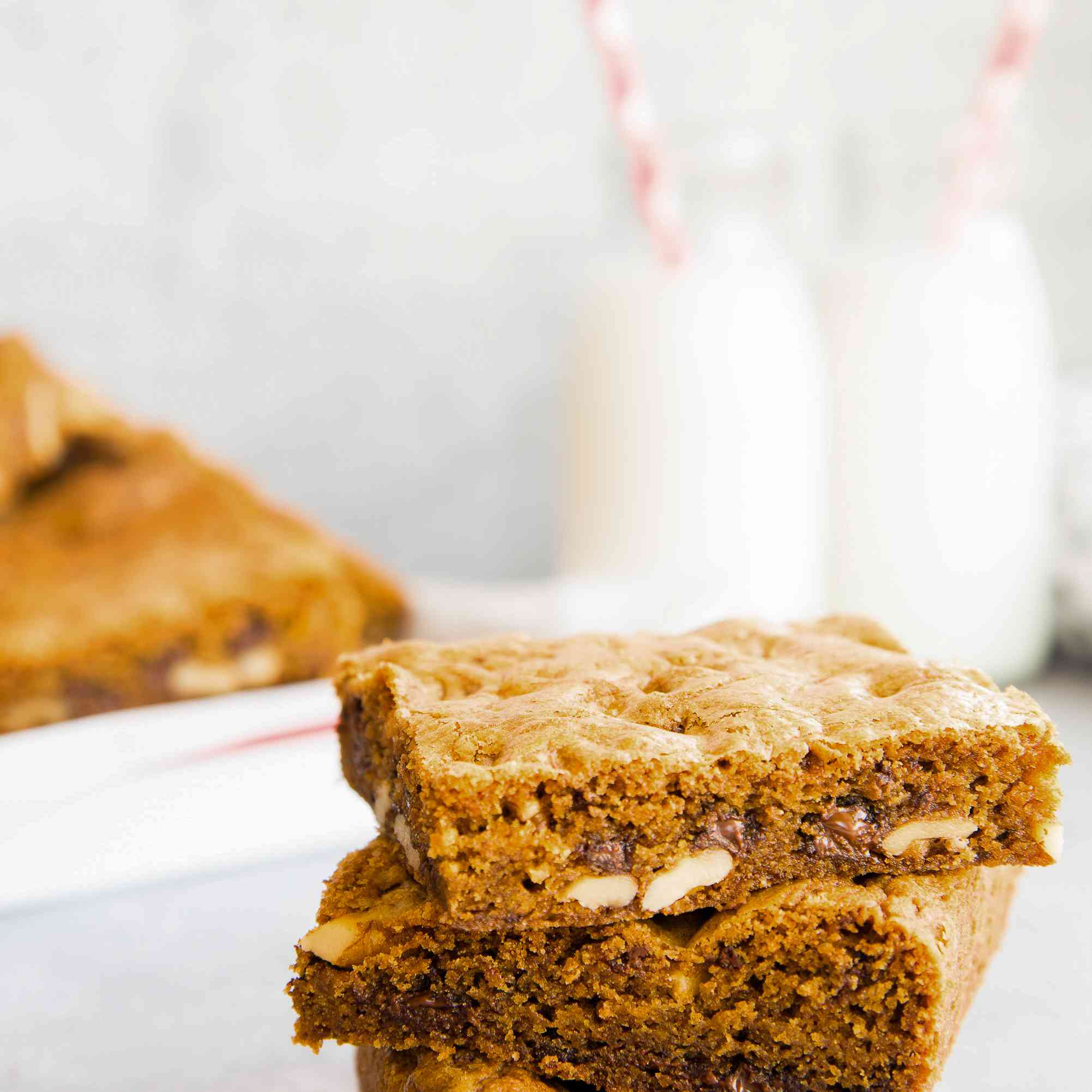 Three chewy chocolate chip cookie bars on a napkin with glasses of milk behind it.