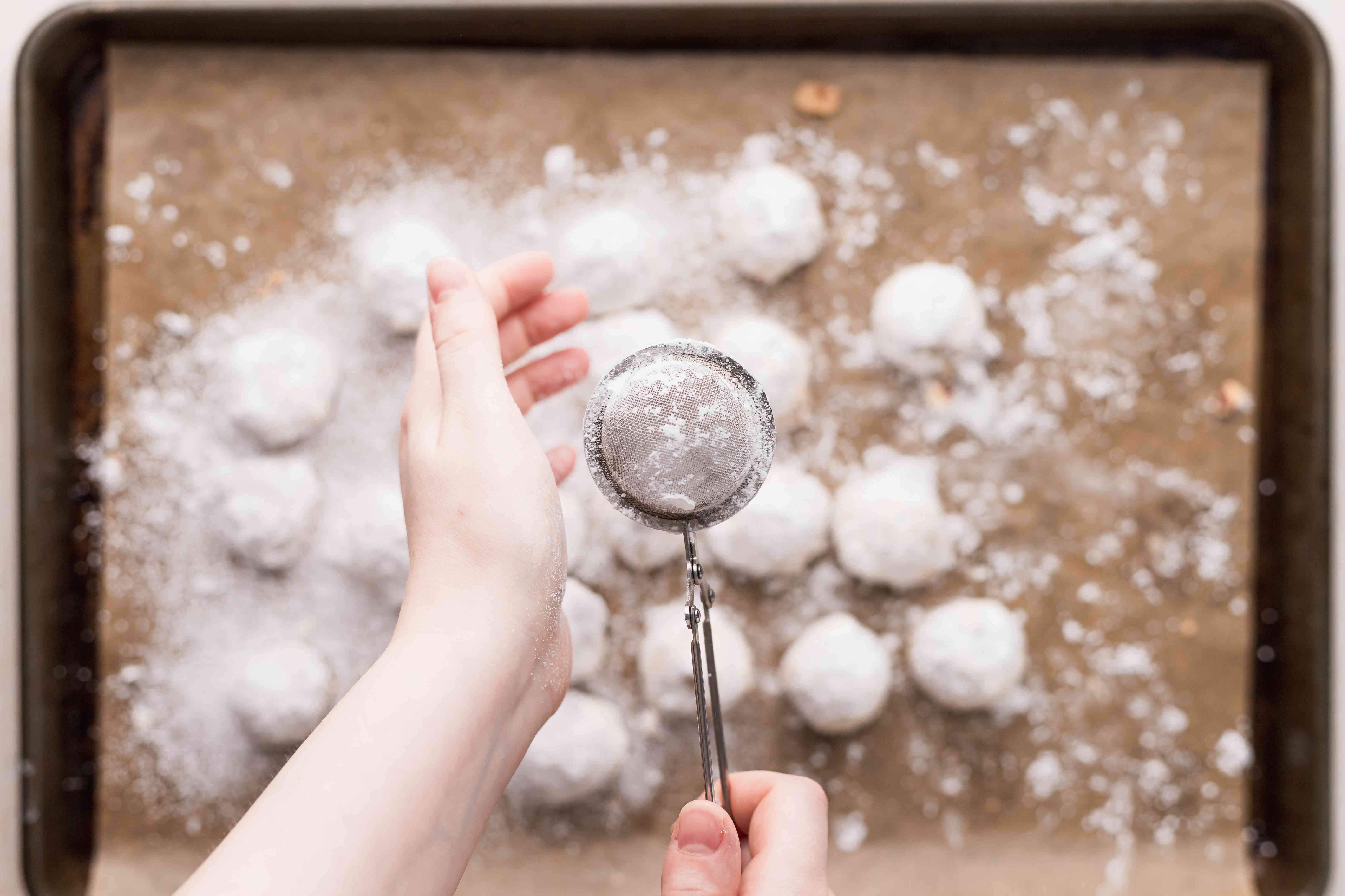 Dusting powdered sugar cookies with powdered sugar.