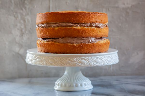 Secrets for the perfect layer cake with a three layer cake on a cake stand.