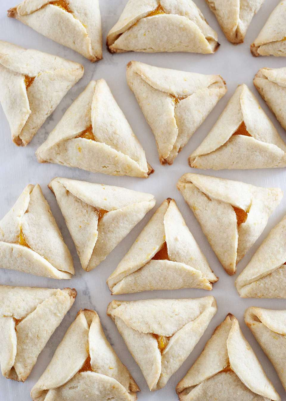 Close up view of Apricot Hamantaschen set in a circular pattern on a white background.