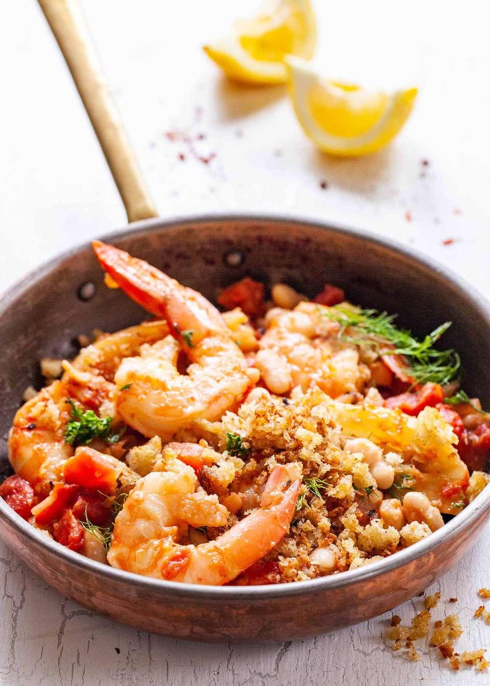 Weeknight Shrimp Dinner - shrimp, breadcrumbs, vegetables, tomatoes and beans in skillet with lemon wedges