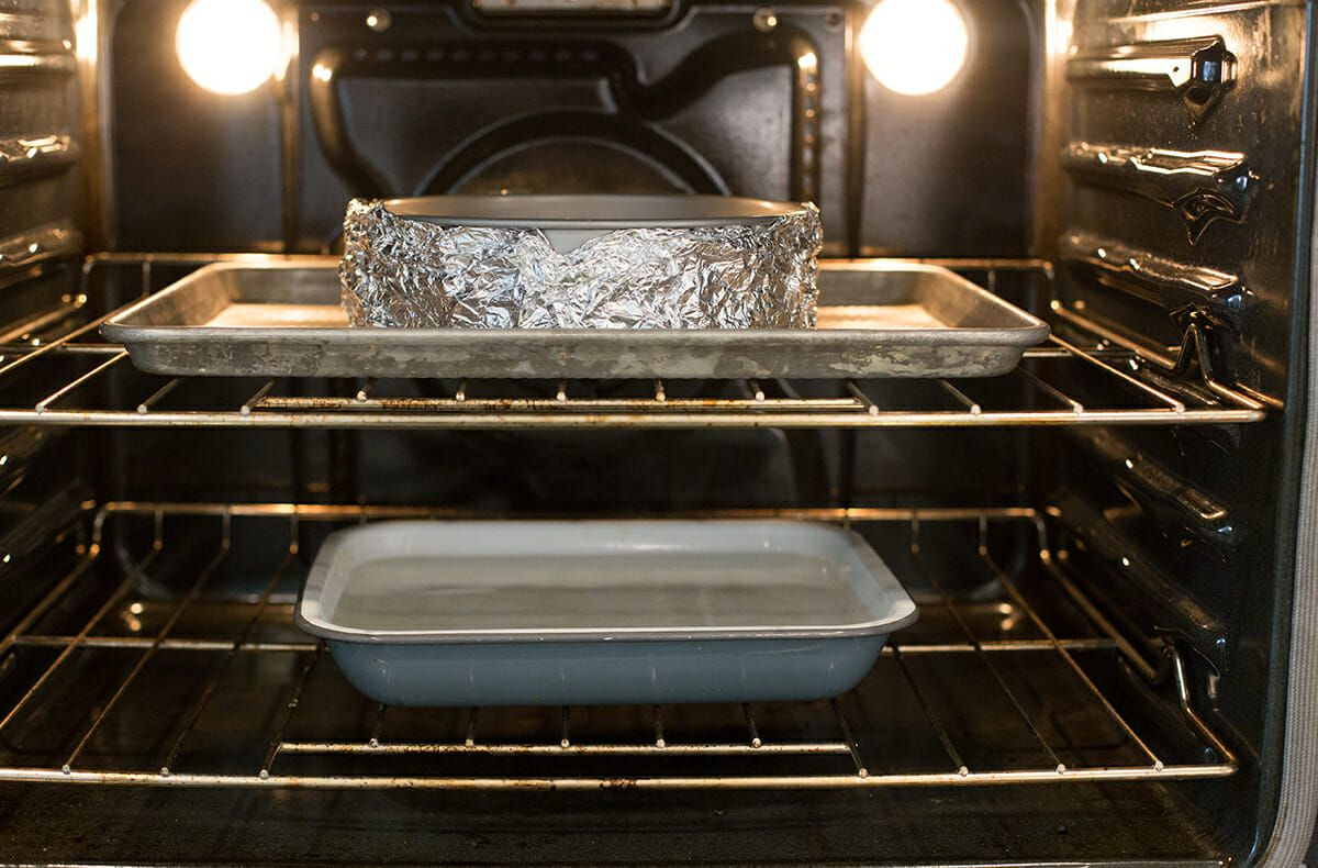 Cheesecake Recipe with Lemon - pan of water in oven with cheesecake on sheetpan on upper rack