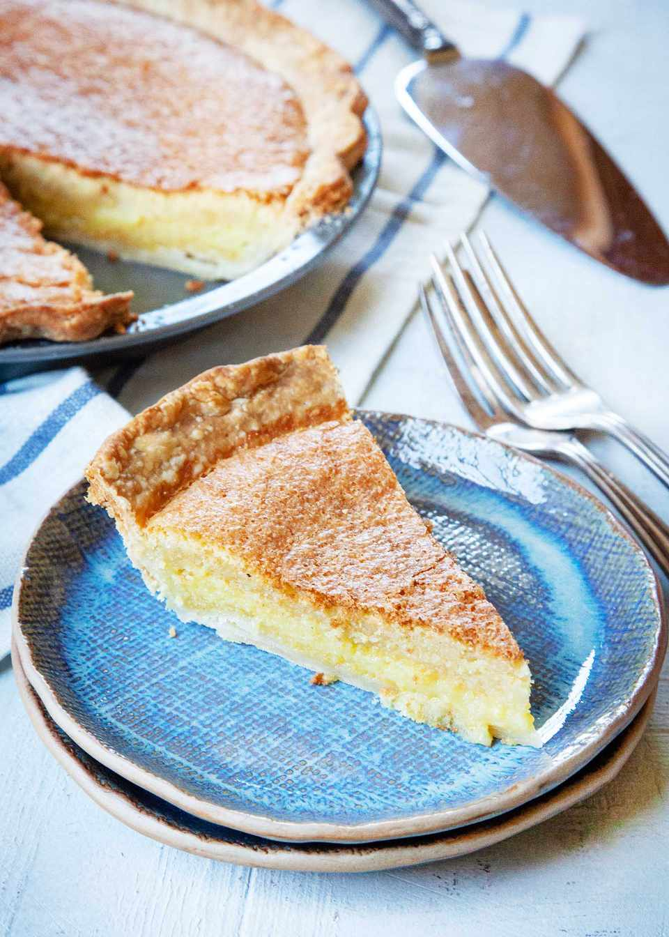 A slice of chess pie on stacked blue plates. Forks are set to the right and the rest of the pie is behind it.