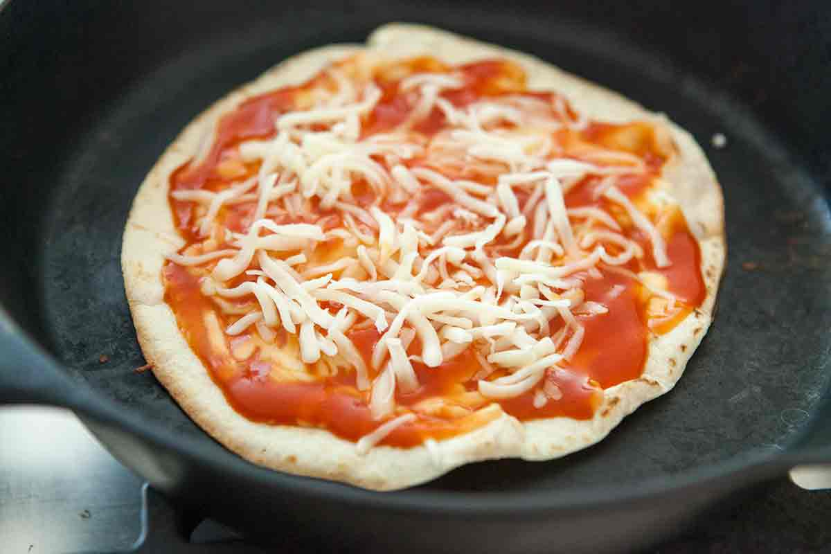 tortilla pizza in cast iron pan with toppings