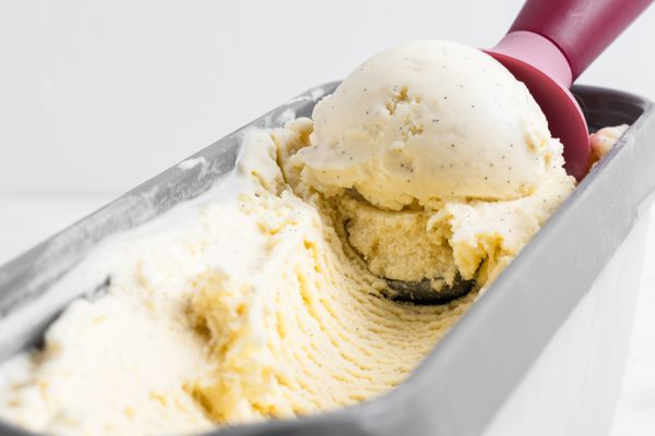 Scooping vanilla ice cream out of a container.