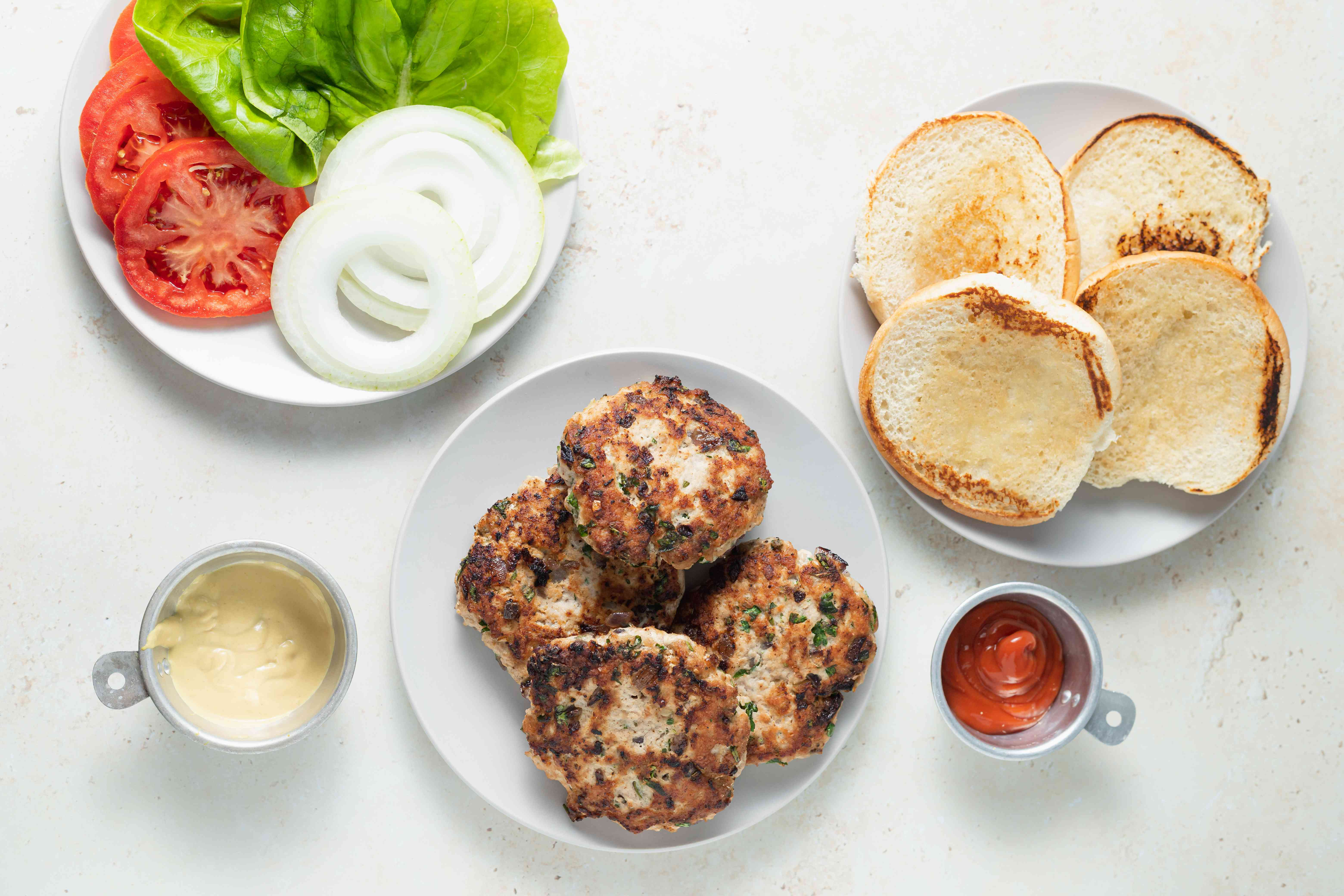 Plates with toasted buns, turkey burgers, and toppings for the best turkey burger recipe.