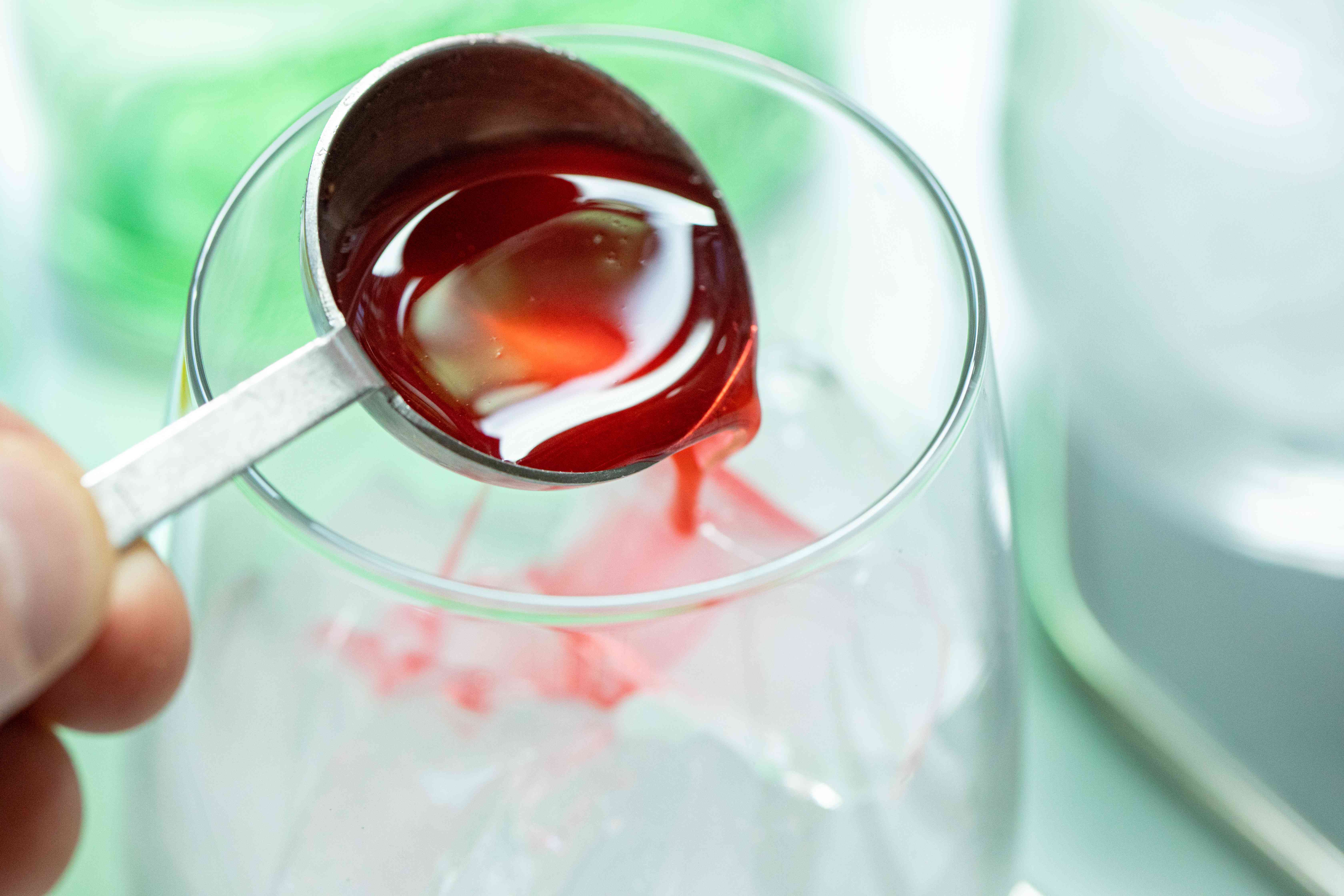 Adding raspberry syrup to an ice filled glass to make Raspberry Ranch Water