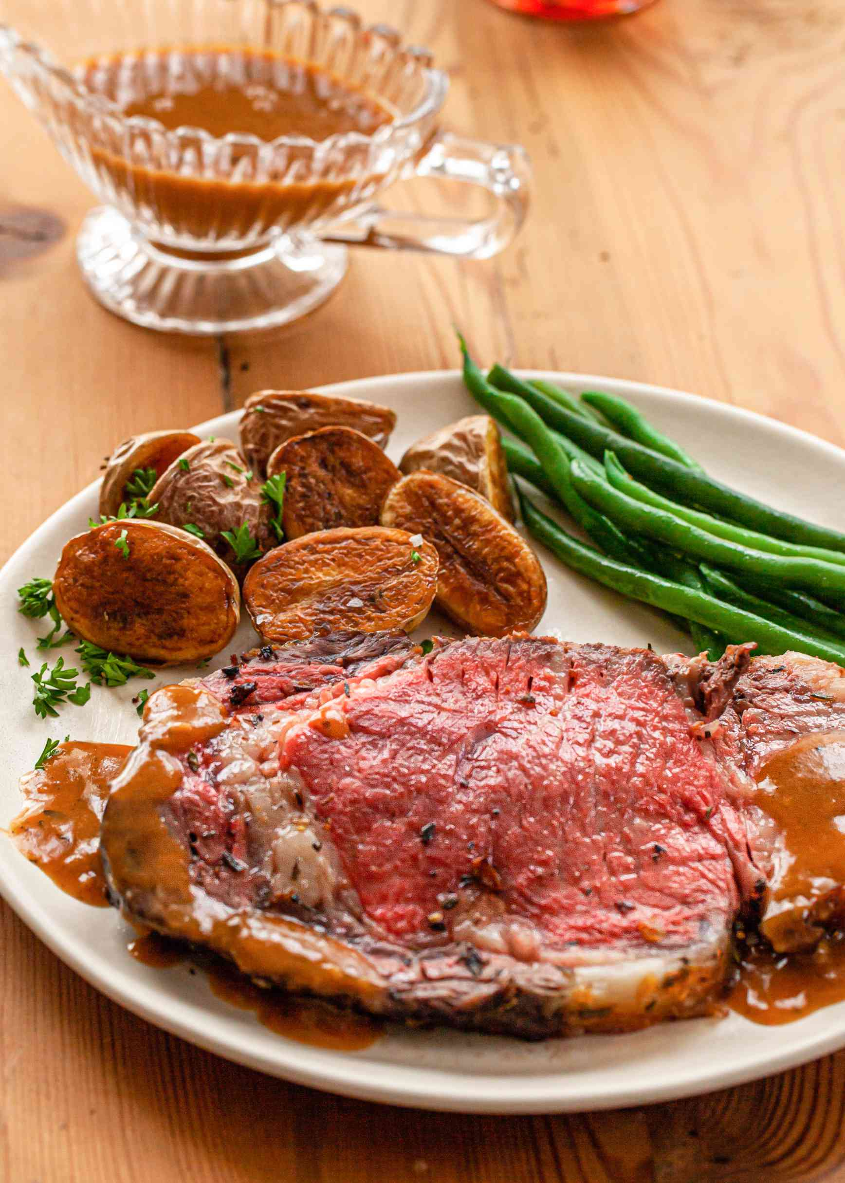 Prime Rib with Thyme, Rosemary, Shallot Herb Butter on a plate with green beans and potatoes.