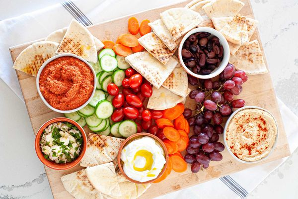 Dips vegetables fruit and olives for mediterranean mezze platter