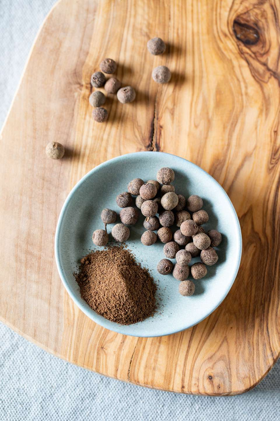 Whole and ground allspice on wooden cutting board