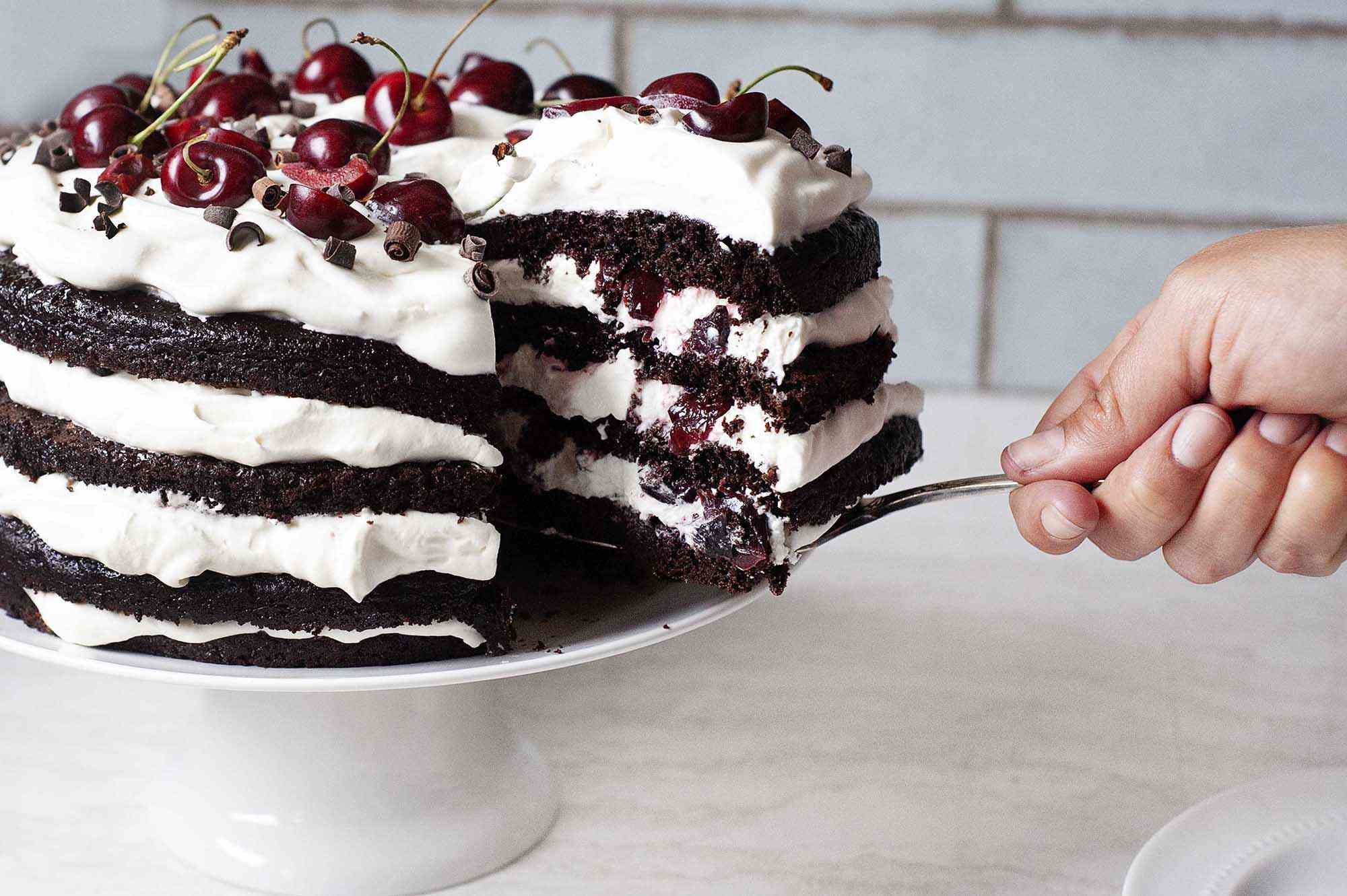 Homemade Black Forest Cake with a slice being removed.