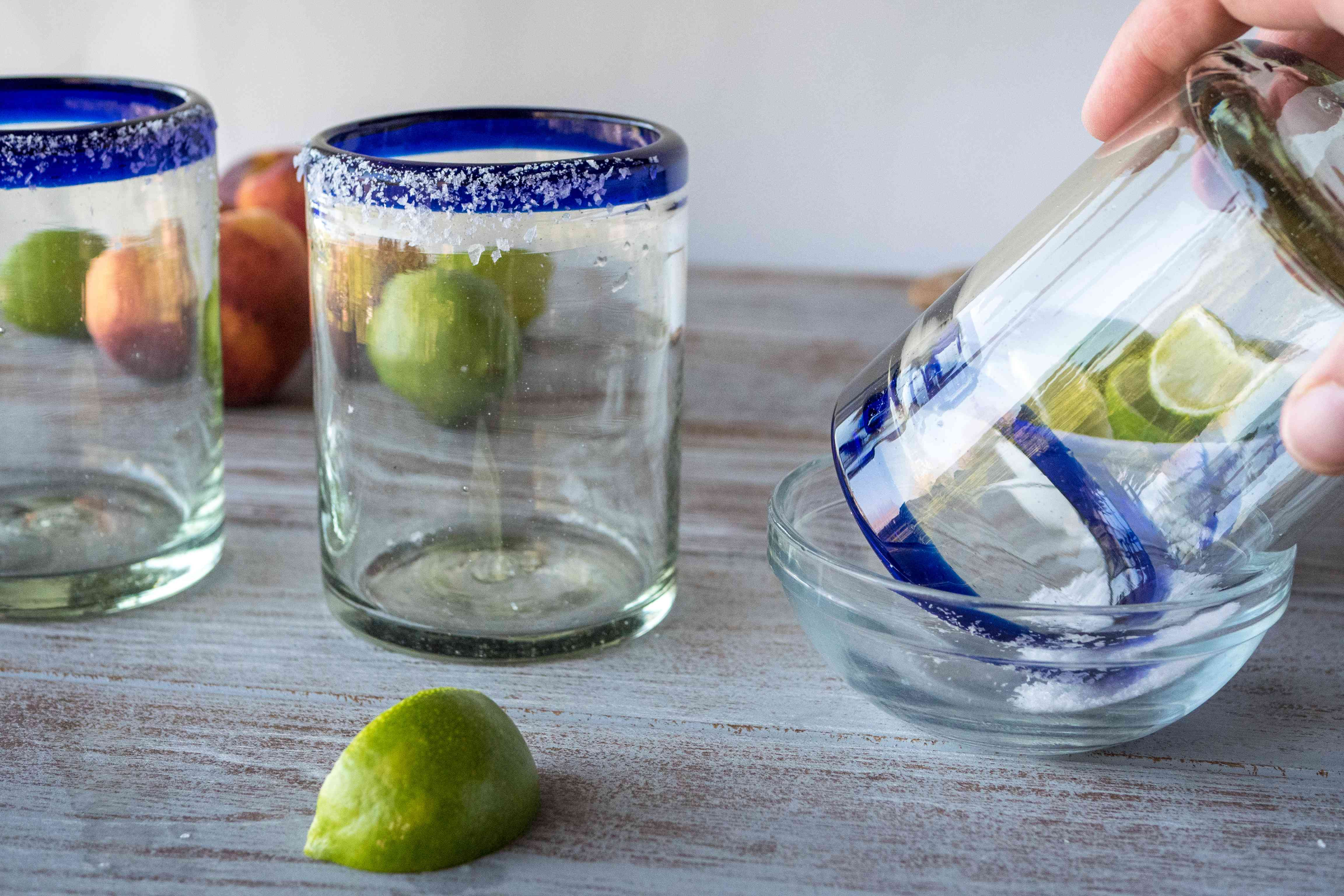 Adding salt to the rim of a glass to make margaritas.