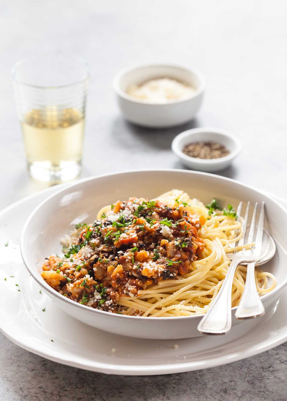 Cauliflower Bolognese in a bowl with spaghetti and silverware. A plate is under the bowl. A drink, grated parmesan and ground pepper are behind it.