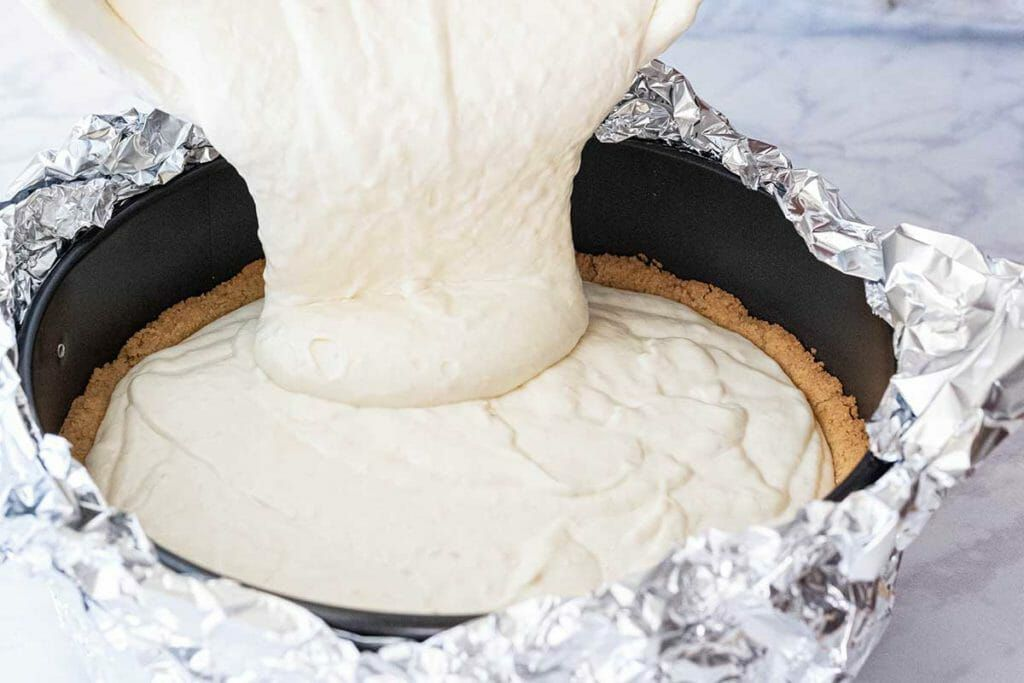 Banoffee Pie Cheesecake - Pouring batter into pan, aluminum foil on side