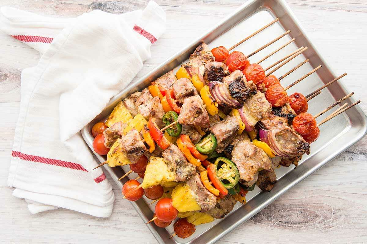Pork kebabs with grilled pineapple on a quarter sheet pan.