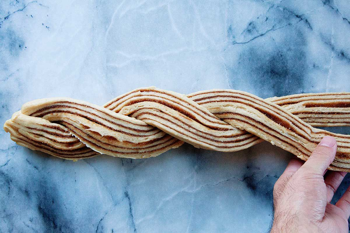 The halved homemade King Cake dough is being twisted on a marble background.