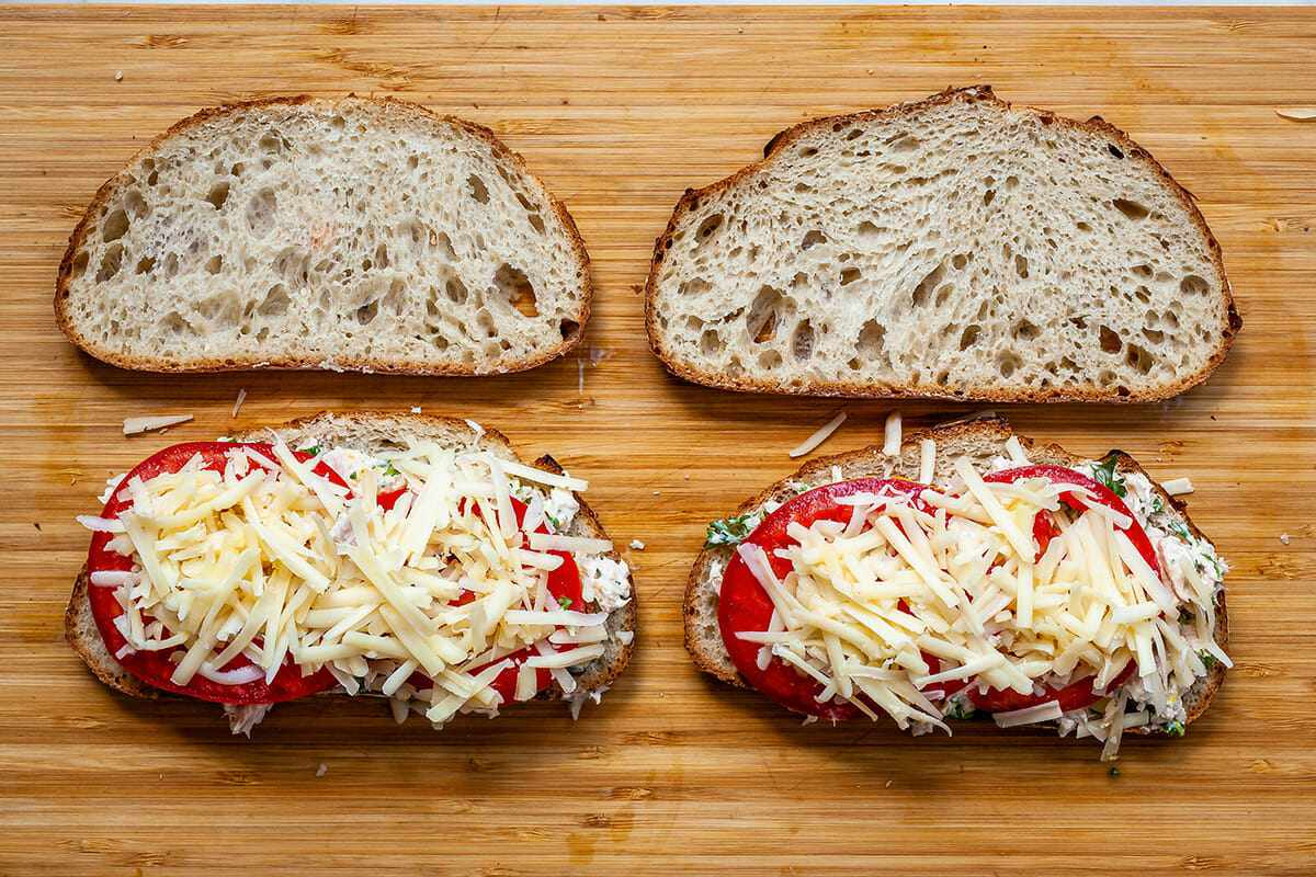 How to make a tuna melt. Four pieces of sturdy bread laid out on a wooden cutting board and two of the pieces have tuna salad, sliced tomatoes and shredded cheese on top.